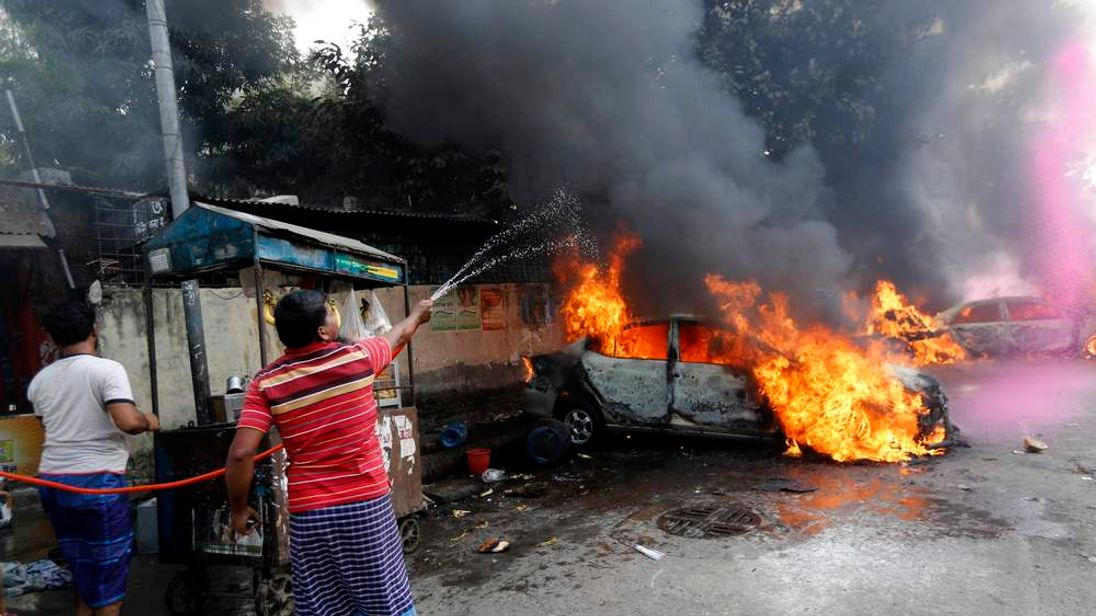 Street vendors use a hose to spray water on a vehicle that was torched by Jamaat-e-Islami party activists during clashes with police in Dhaka