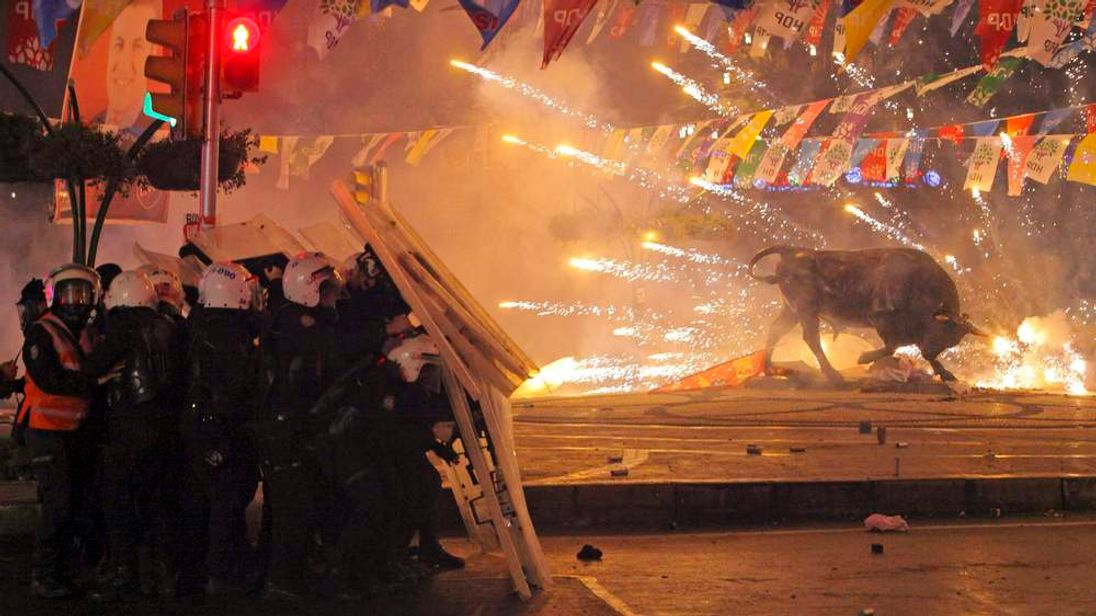 Riot policemen shield themselves as fireworks thrown by protesters explode next to the statue of a bull, during an anti-government protest in Kadikoy