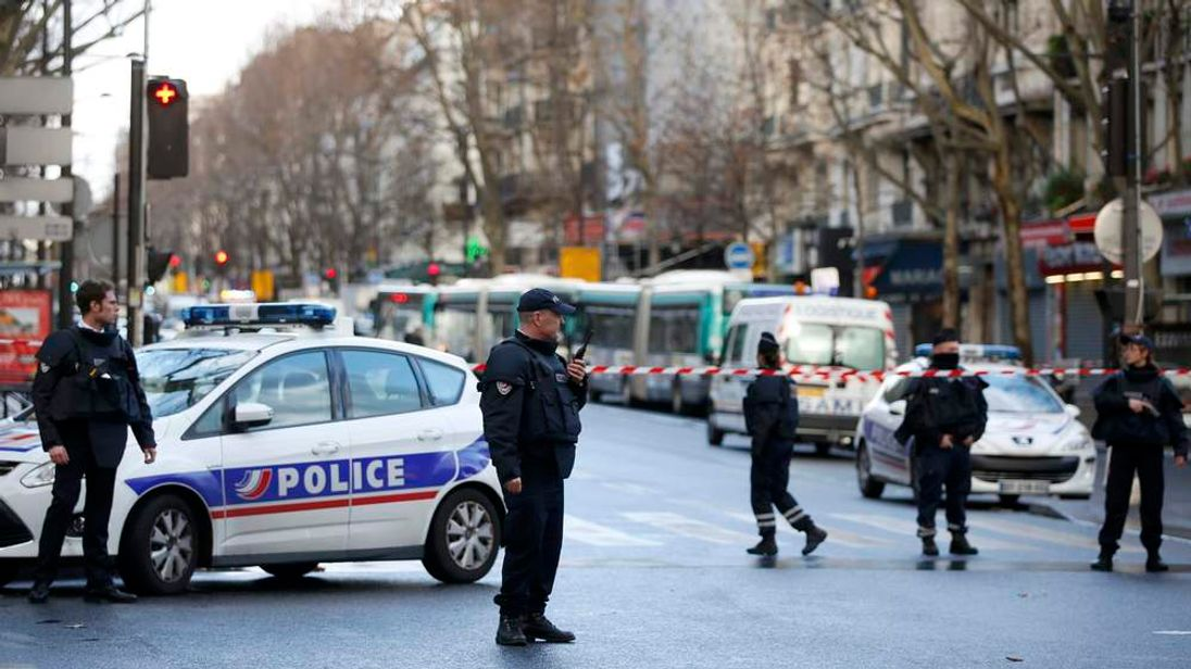 French police secure the area after a man was shot dead at a police station in the 18th district in Paris
