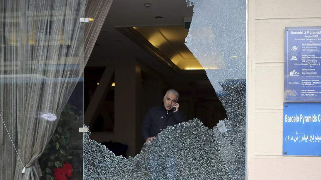 A police investigator is seen through a smashed window at a hotel where gunmen attacked tourists in front of a hotel in Giza