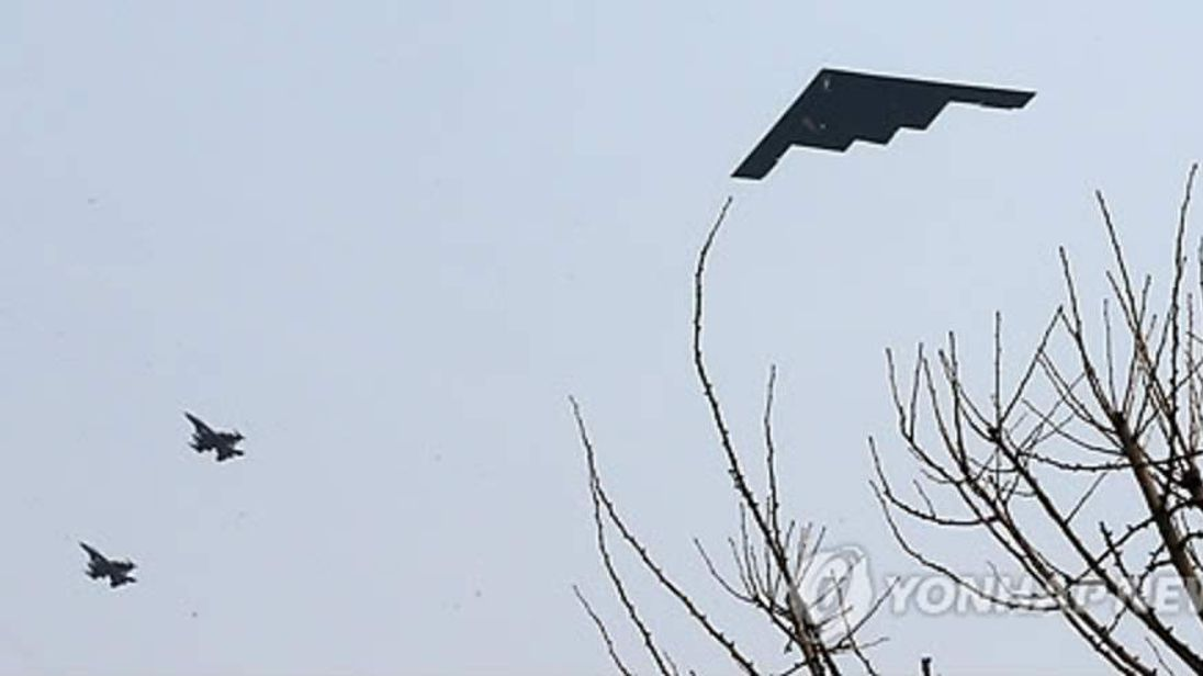 A US B-2 stealth bomber flies alongside other planes above South Korea