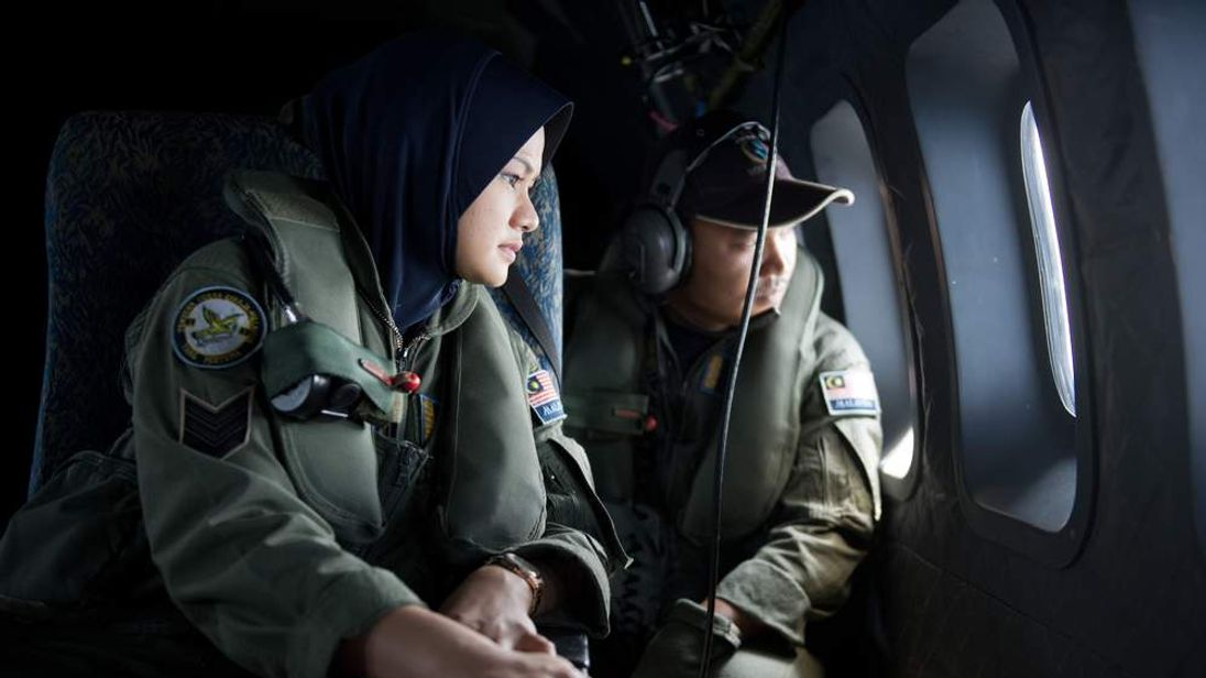Crew members look outside windows from a Malaysian Air Force CN235 aircraft during a search and rescue operation to find the missing Malaysia Airlines flight MH370