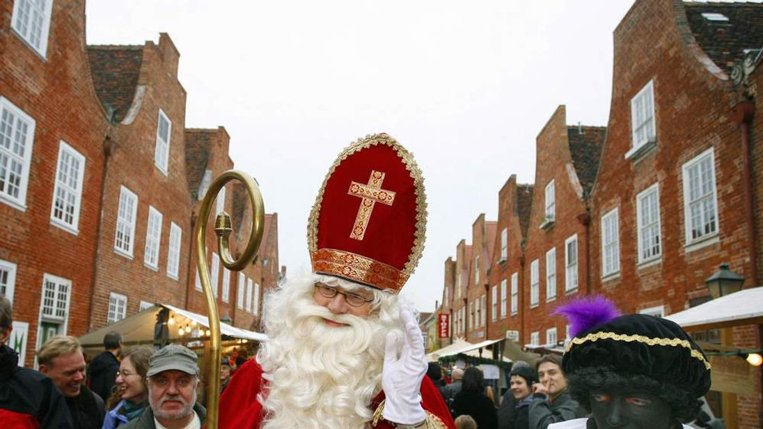 Saint Nicholas and Black Pete walk through the Dutch Quarter of Potsdam, eastern Germany
