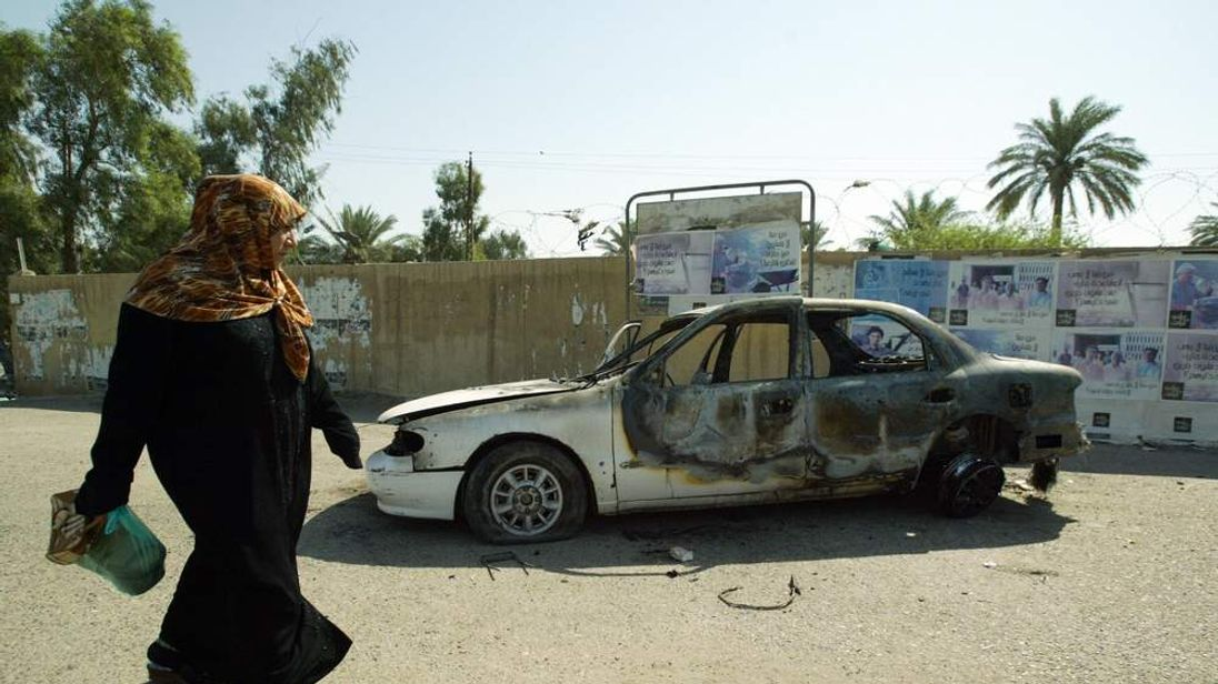a burnt car on the site where Blackwater guards who were escorting US embassy officials opened fire in the western Baghdad neighbourhood of Yarmukh