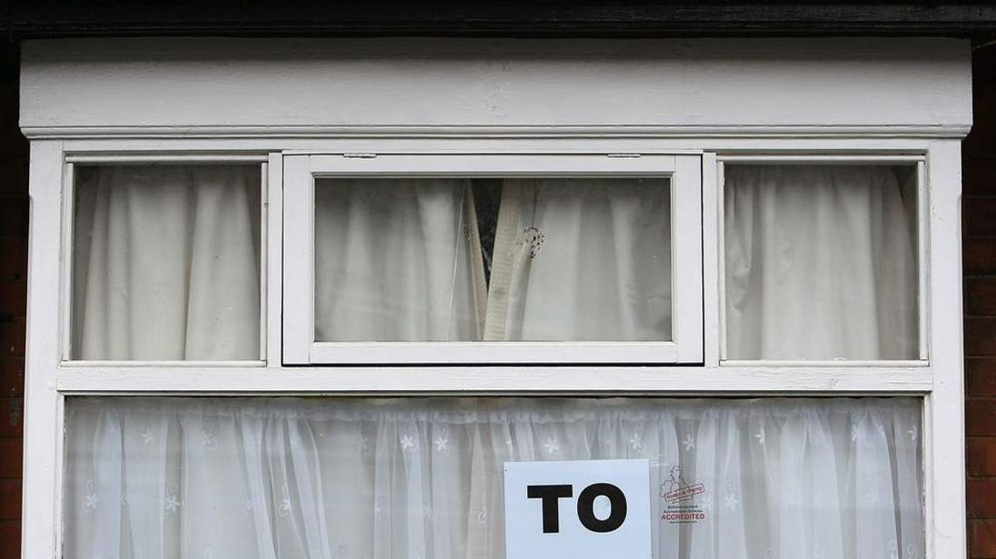 A To Let sign is displayed in the window of a house