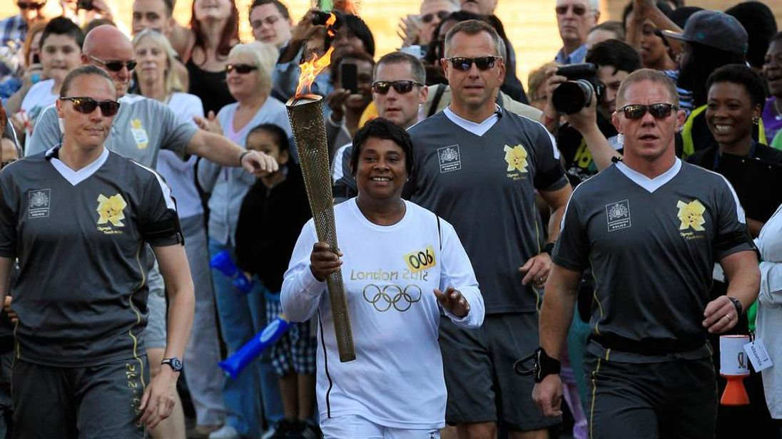 Doreen Lawrence carries the Olympic Torch through south London