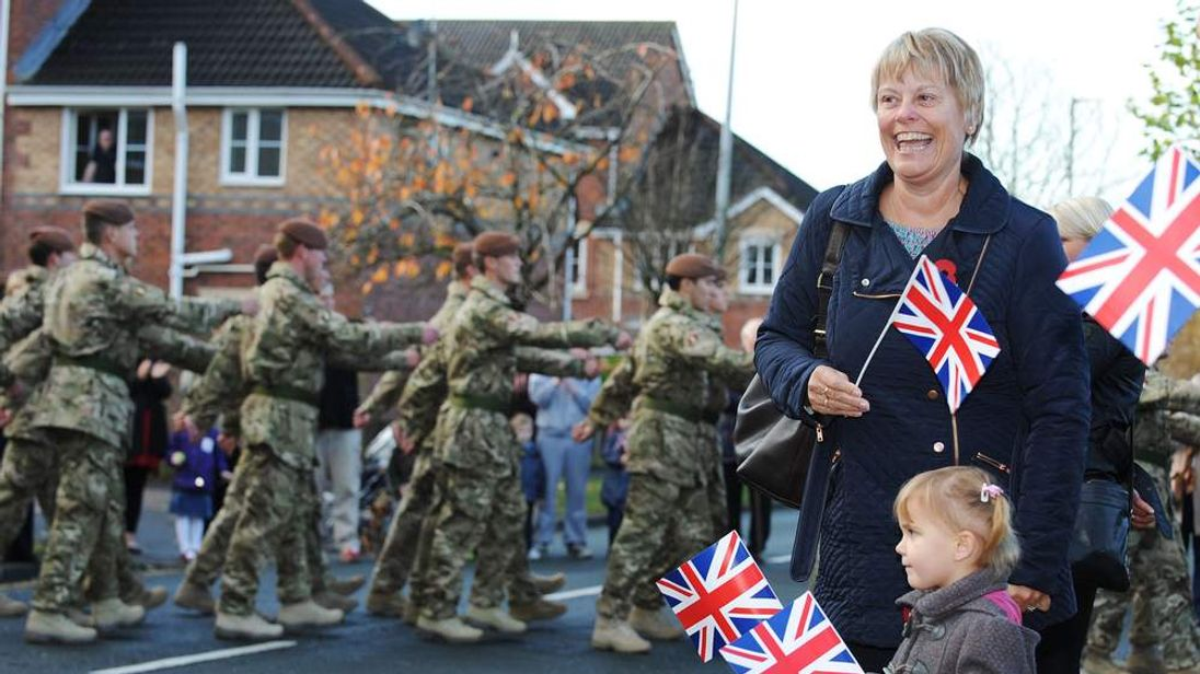 Onlookers waving Union flags at the King's Royal Hussars
