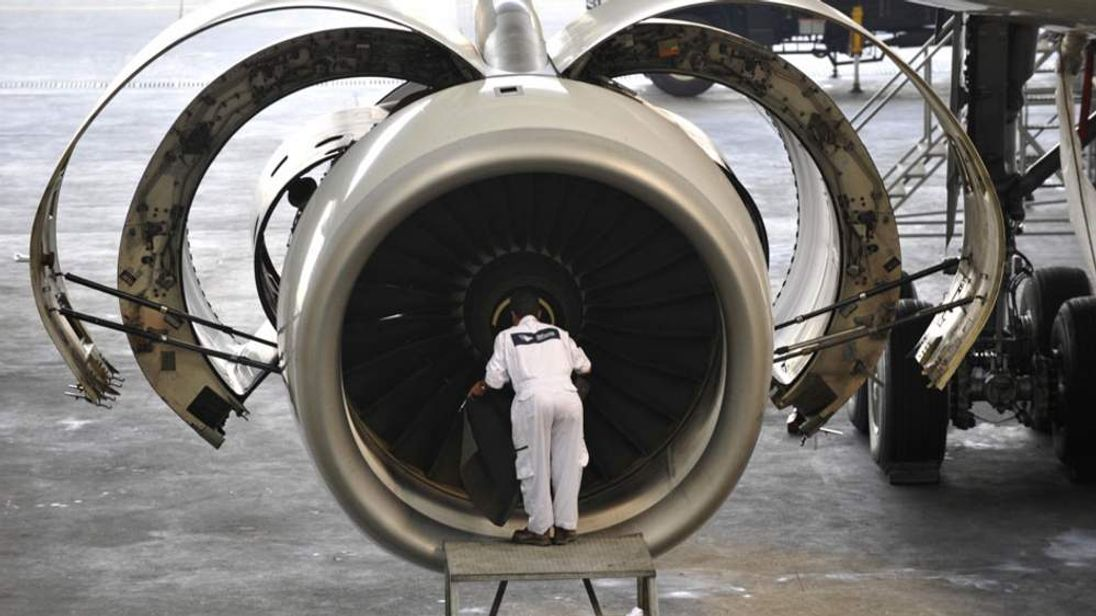 An engineer works on a Rolls-Royce jet engine.