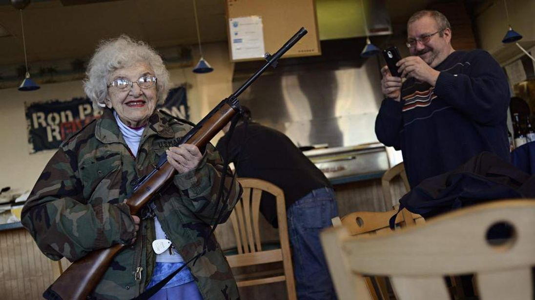 Woman poses with rifle
