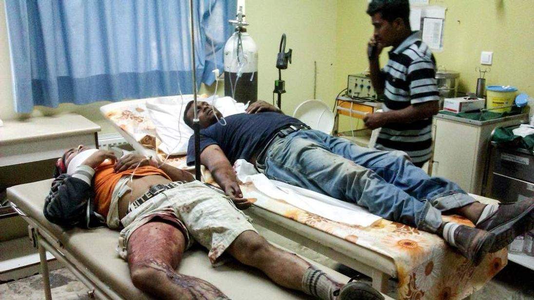 unidentified migrant workers receive first aid at the Medical Center of Varda, in Greece. At least 20 migrant strawberry pickers, most of them from Bangladesh, were shot and wounded in southern Greece on Wednesday, in a pay dispute after a foreman opened fire on them with a shotgun