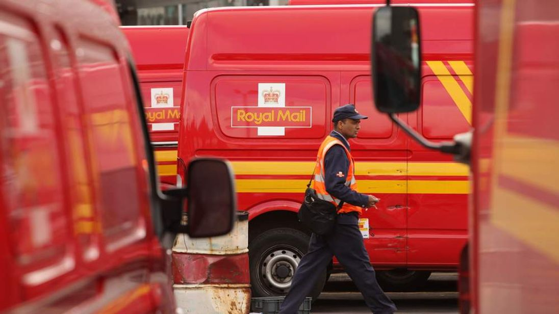 A postman walks in front of a Royal Mail van