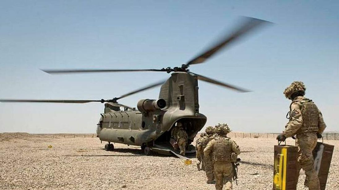 Troops make their way to a helicopter as they prepare to leave FOB Sterga