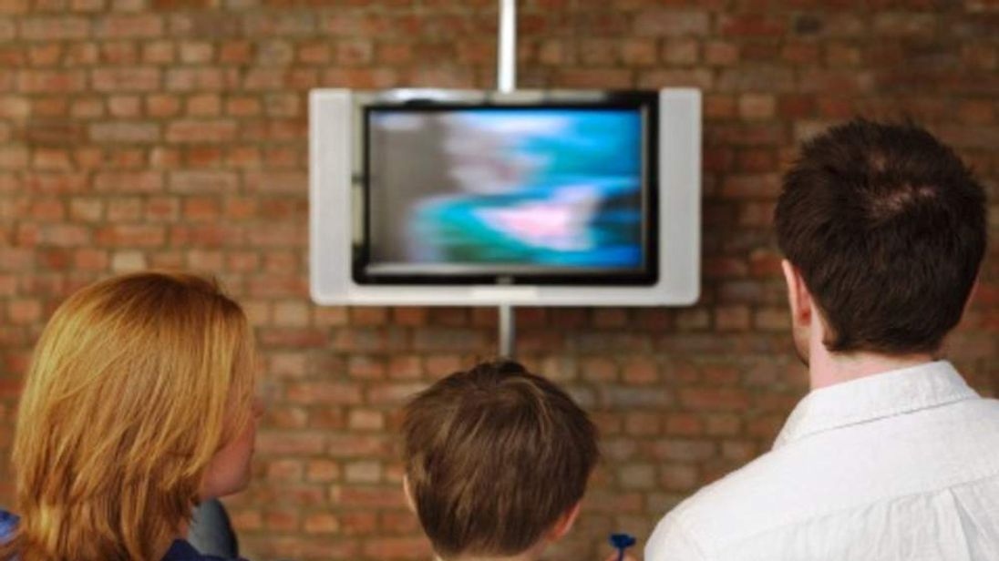 A boy watching TV with his parents