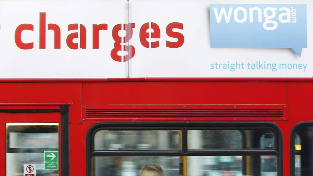 A passenger sits on a bus beneath an advert for short term loan company Wonga
