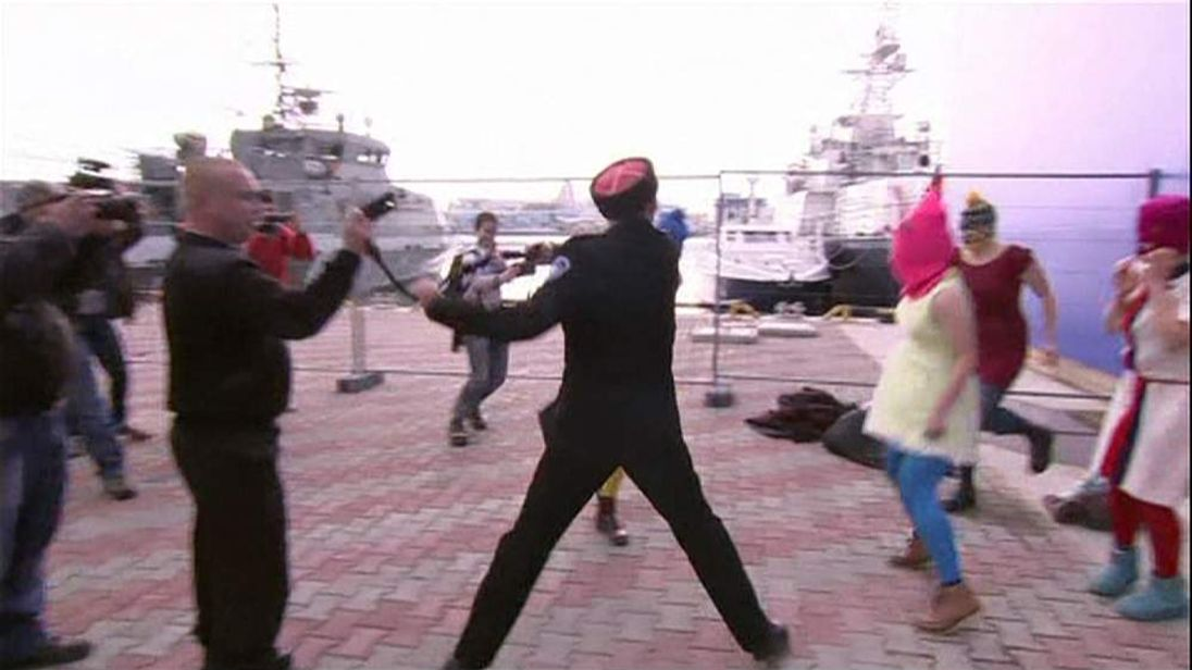 Cossack whips a member of Pussy Riot