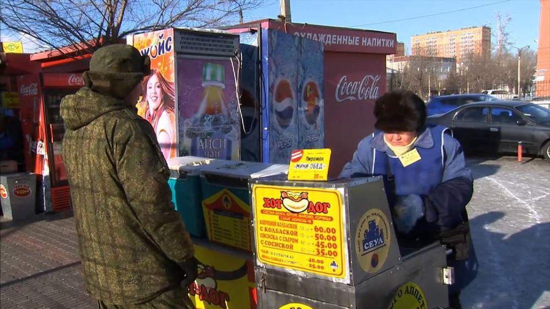 Marina Gennadievna tends her hot dog stall. Sky News on Russian economy.