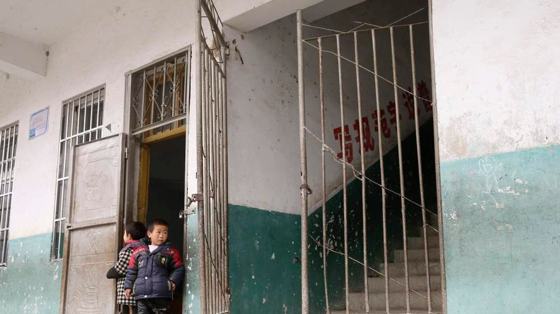 School children stand next to a broken gate of a classroom building where a stampede happened at a primary school in Xiangyang, Hubei province