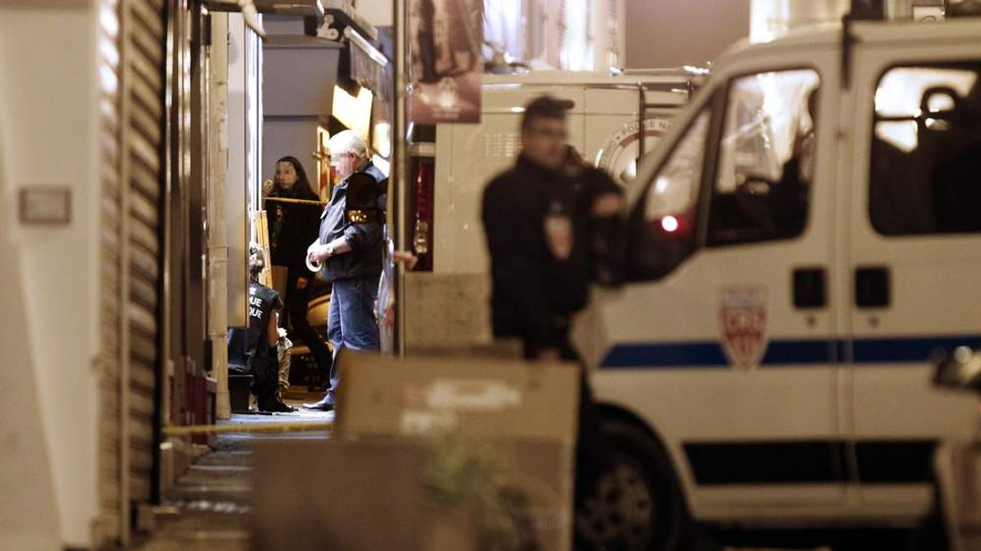 French policemen and forensics investigate around the crime scene