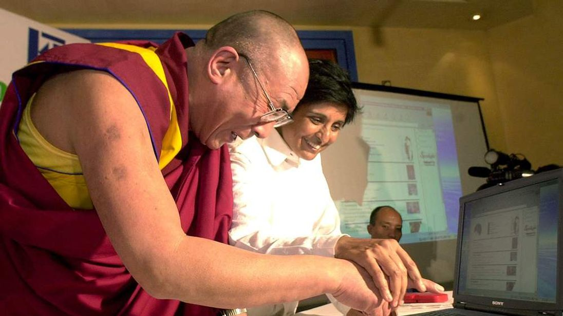 Indian 'Super-Cop'  and Magsaysay award winner Kiran Bedi helps Tibet's exiled spiritual leader Dalai Lama press the right key on a laptop computer
