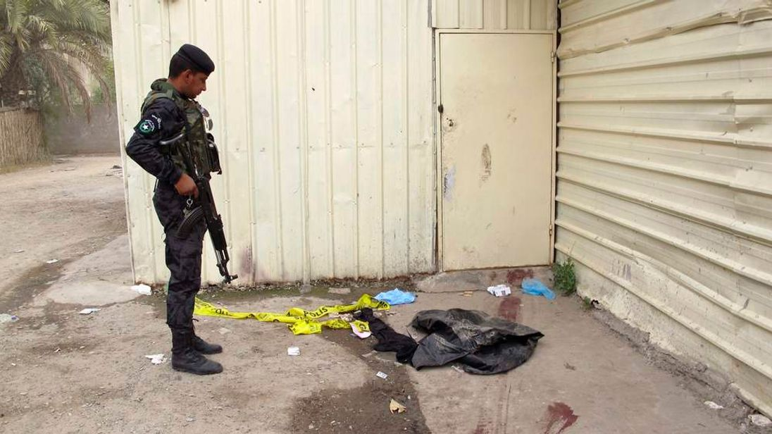Police outside an apartment where 29 were shot dead in Baghdad