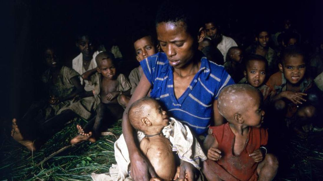 A woman with her children waits for food