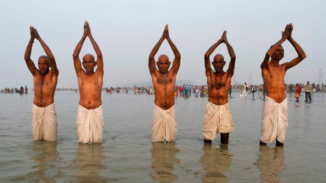 Hindu pilgrims pray to the Sun God before taking a holy dip at the confluence of the river Ganges and the Bay of Bengal at Sagar Island