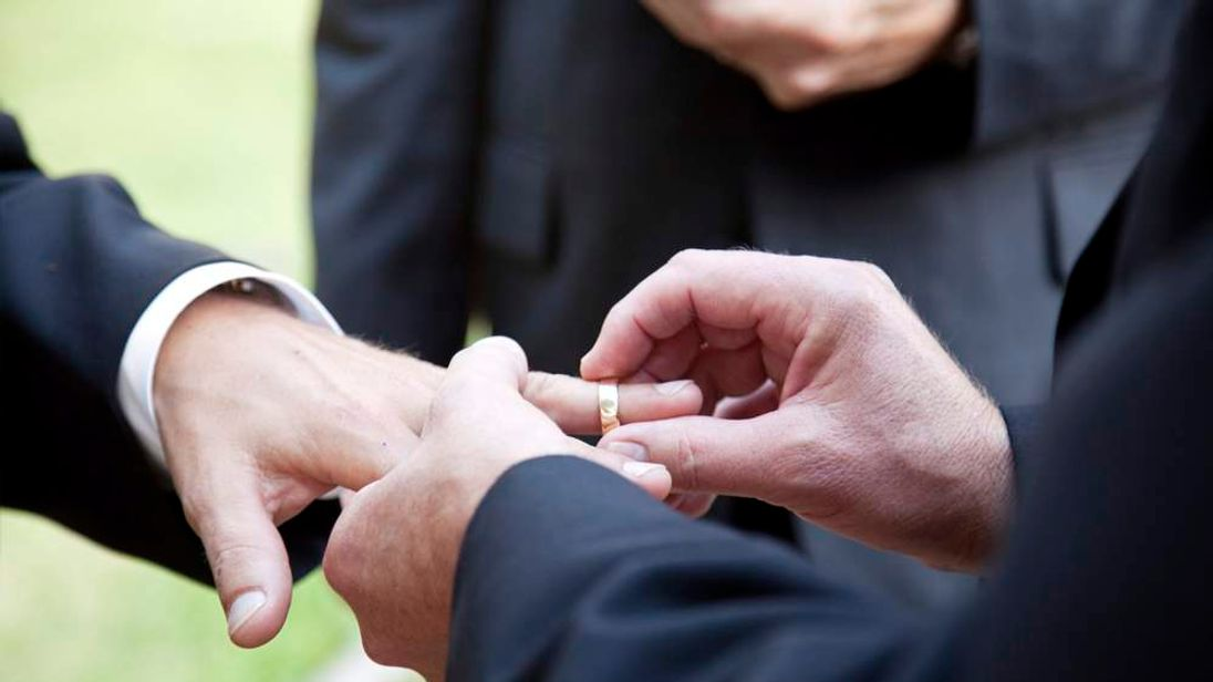 A gay couple exchange wedding rings
