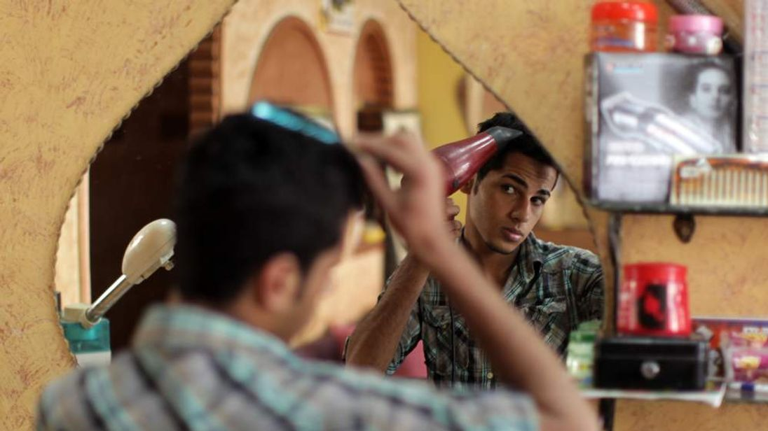 A Palestinian youth dries his hair after getting a haircut at barber's shop in Gaza City