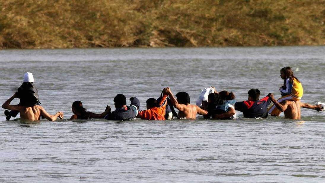 Immigrants, including children, illegally cross the Rio Bravo into the US