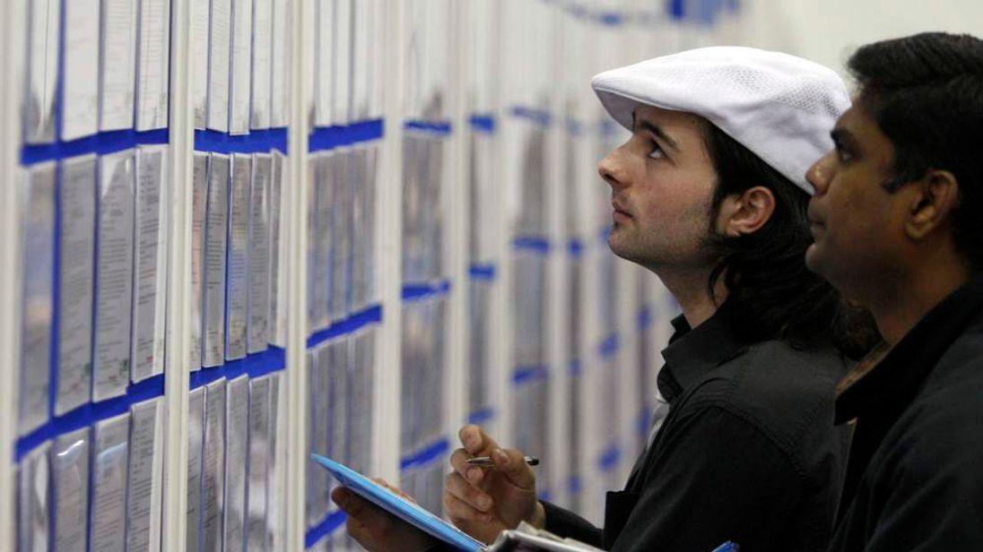 People look at jobs listings at a careers fair