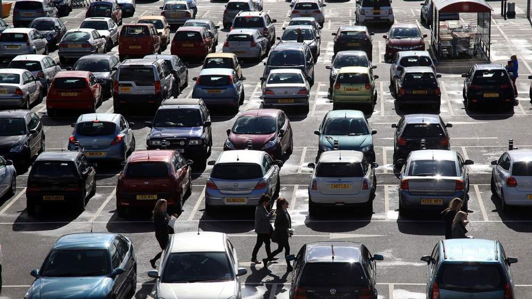 Shoppers walk between cars at a supermarket car park