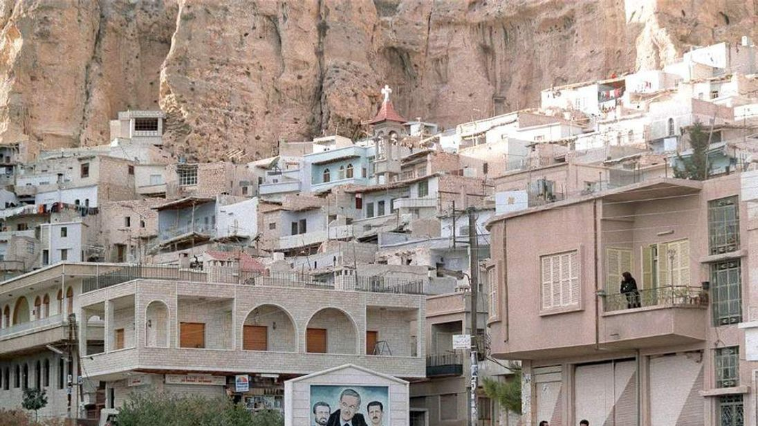 Syrians walk in one of the streets of village of Maaloula