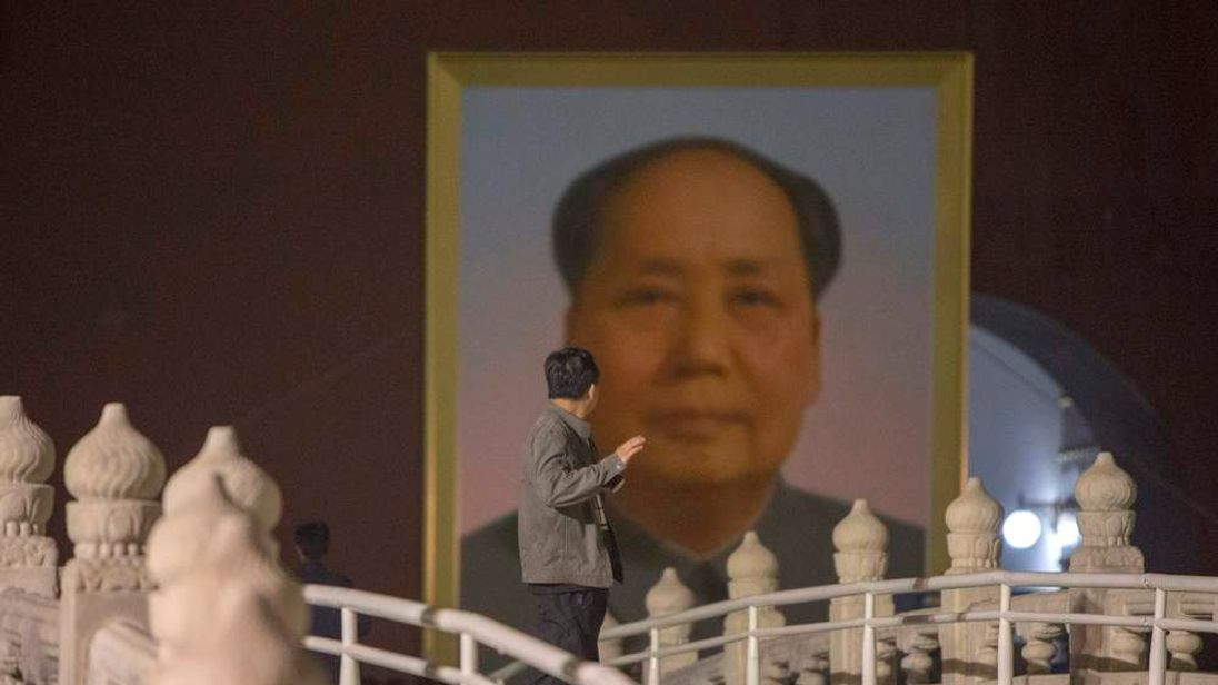 A worker looks at the new portrait of China's late Chairman Mao as it is moved into place to replace the old one at Tiananmen Gate during annual renovation works before the country's national day in Beijing