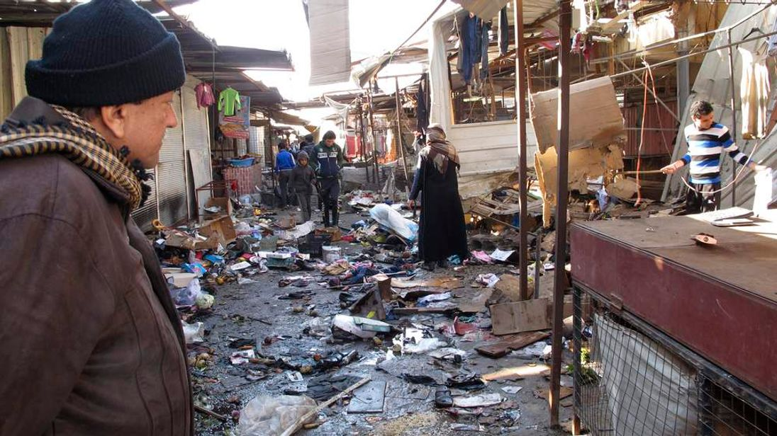 A man looks at the site of bomb attack at a marketplace in Baghdad