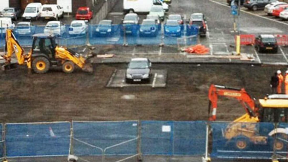 A car left in the middle of a worksite in a car park at Edinburgh Waverley station.