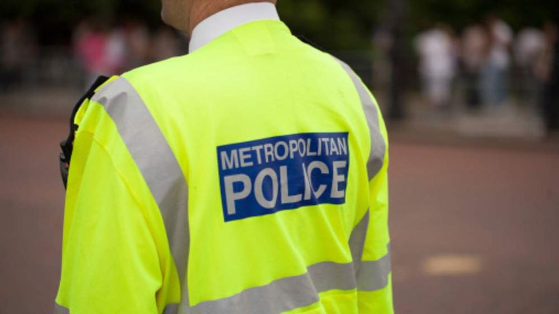 A picture showing the back of a policeman with a Metropolitan Police sign on his back