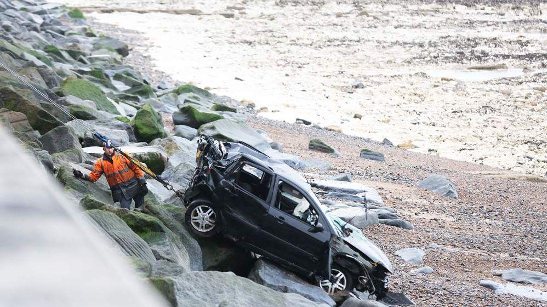 A man drives his car off an 80ft cliff.