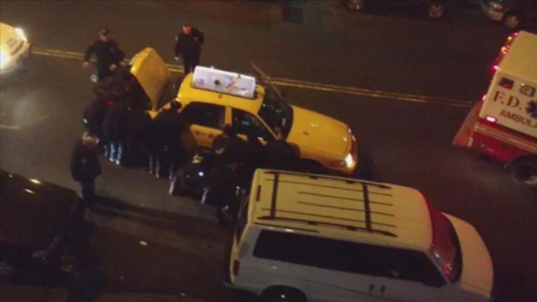 New York cops lift taxi off an injured man