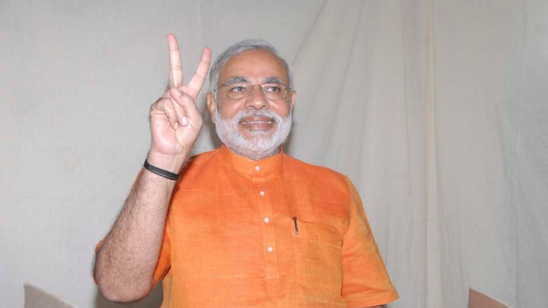Gujarat state Chief Minister Narendra Modi gestures as he casts his vote during the second phase of state elections in the western Indian city of Ahmedabad