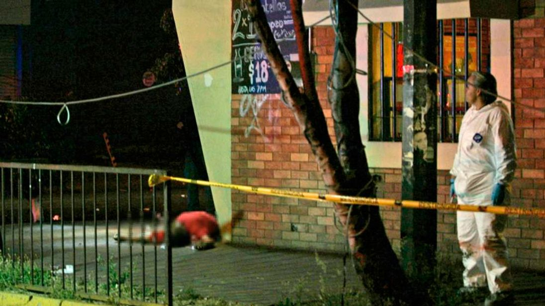 Member of a forensic team stands near the body of a man outside a bar at a crime scene, after an attack by unidentified gunmen in downtown Guadalajara