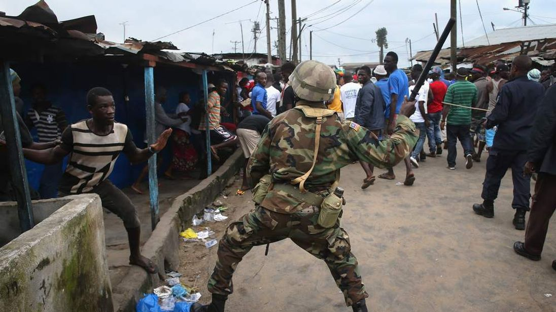 A Liberian Army soldier, part of the Ebola Task Force, clashes with a local resident while enforcing a quarantine on the West Point slum
