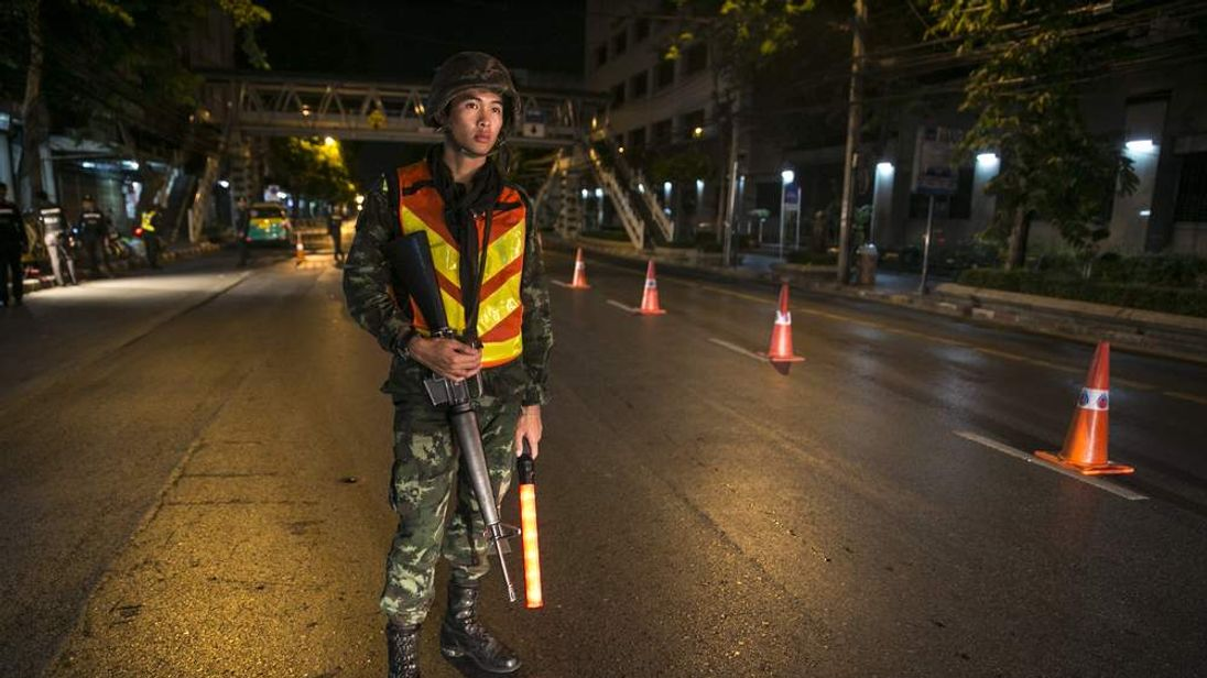 A soldier stands guard at a checkpoint after the curfew starts