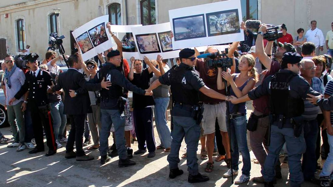Policemen stand guard as demonstrators protest the deaths of hundreds of migrants in last week's Lampedusa boat disaster, in Lampedusa