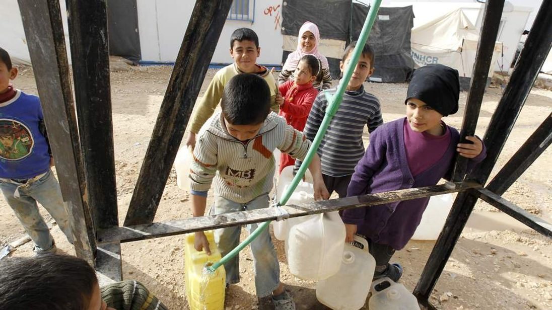 Young Syrian refugees collect water at Al-Zaatri refugee camp in Mafraq