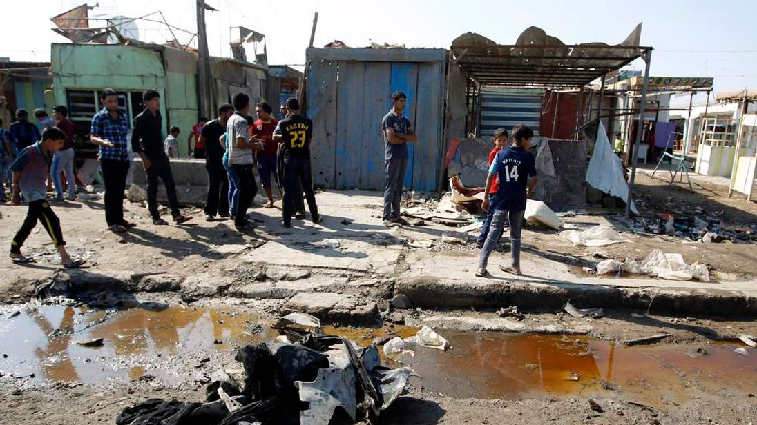 Residents inspect the site of a bomb attack in Baghdad.