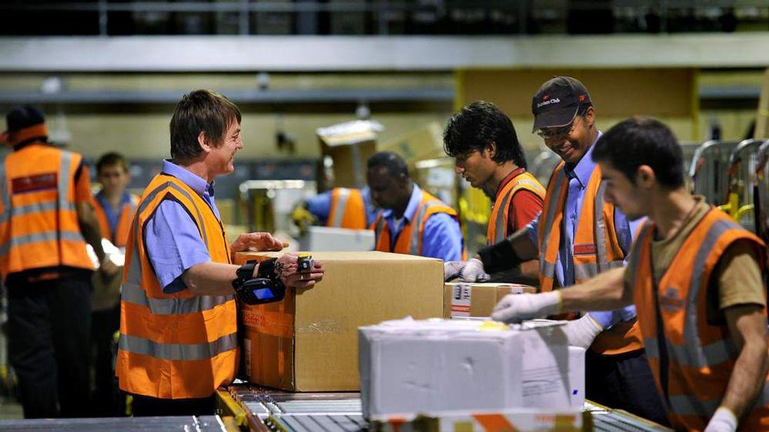 Royal Mail staff sort parcels at central distribution centre