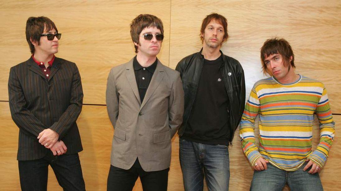 Members of British rock band Oasis pose at news conference in Hong Kong