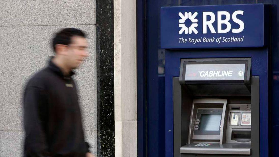 A pedestrian passes a Royal Bank of Scotland cash machine in London