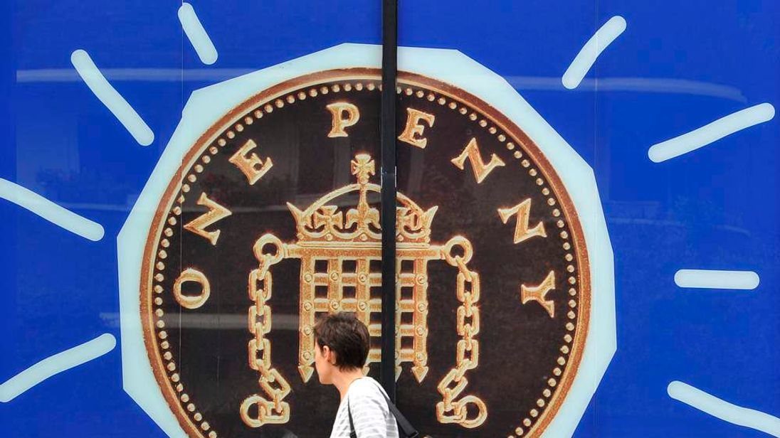 A woman passes a window advertisement showing a one pence coin in west London