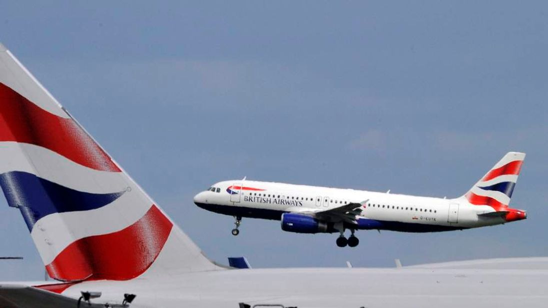 A British Airways plane flies intoHeathrow Airport in west London
